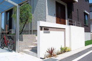 凹凸のラインが特徴の門塀。道路際から玄関ポーチを隠すことでスマートなデザインになりました。
