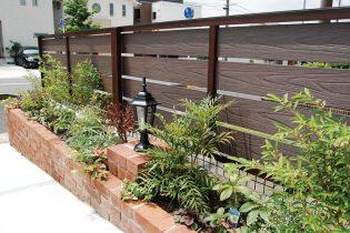 オレンジのレンガを使った花壇と隣地境界を遮る樹脂製のフェンスの組み合わせ。