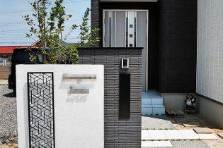 黒いタイル、ポスト、幾何学模様のアクセントパネルに白の塗り壁の門柱のコントラストが美しい造形。