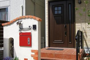 こだわりの手すり、サイン、レンガを使った欧風エントランス。 印象的な赤いポスト内蔵の宅配ボックスが機能的です。