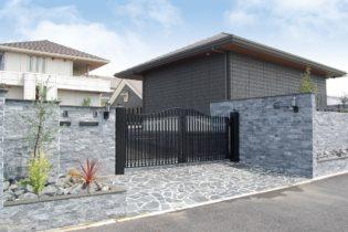 大型鋳物門扉の重厚感と自然石をふんだんに使った格調高いエントランス