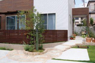 個性的な門柱とウッド調フェンス