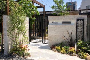 ナチュラルモダン<br />エレガントな風合の天然石タイルとアクセントに鋳物デザインパネルを使ったエントランス。 夜は植栽スペースのLEDライトがエレガントな壁面をさらに演出します。